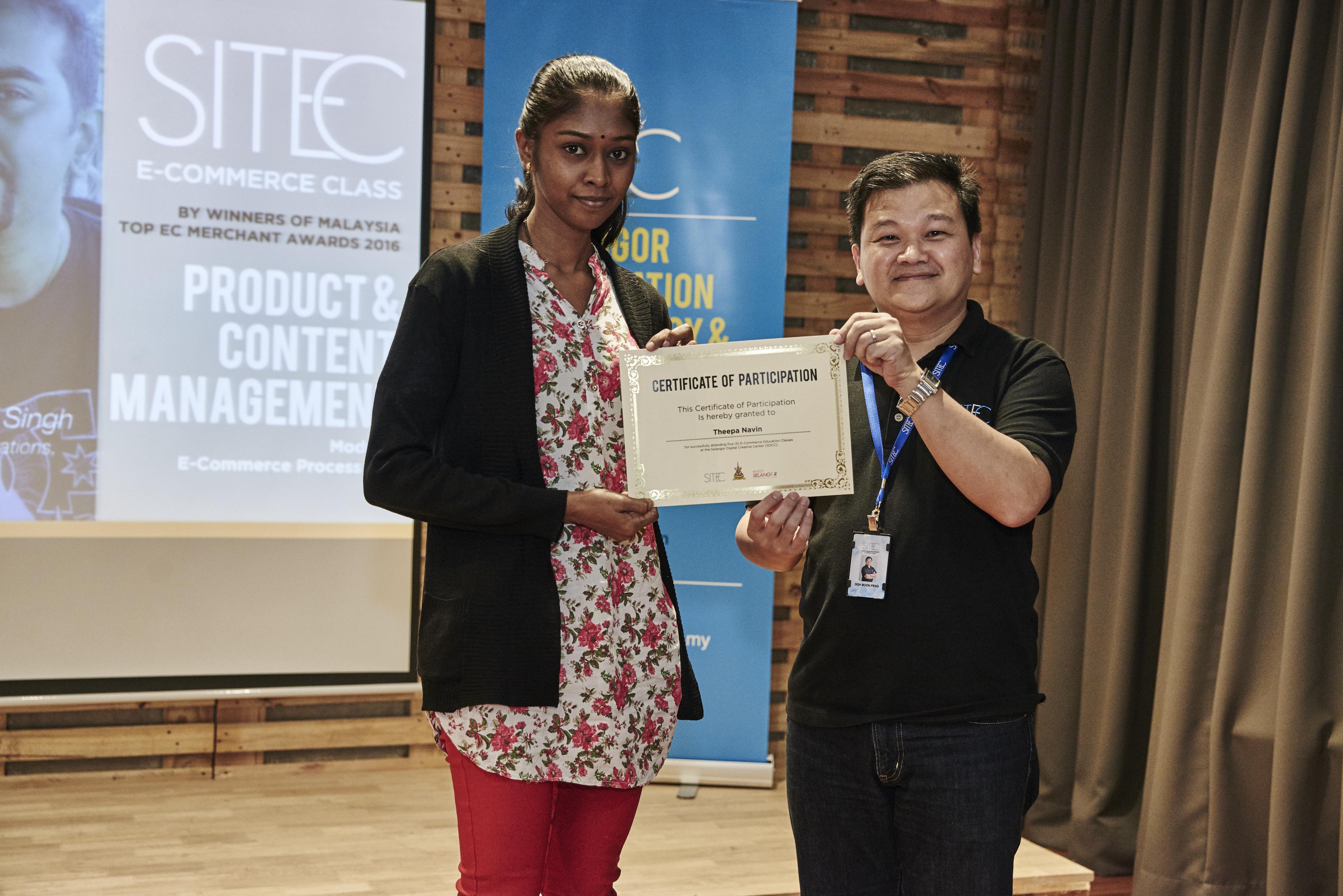 Theepa Navin receiving a Certificate of Attendance from the EC Class Manager, Goh Boon Peng