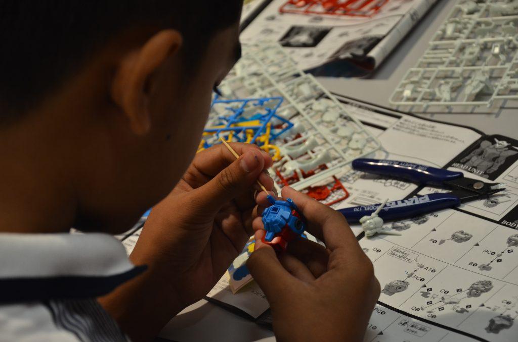 A child assembling the torso of a Gundam mecha